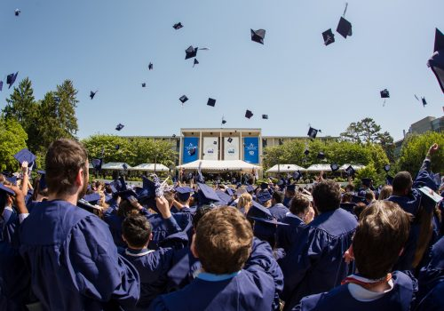 Hat toss from behind graduates