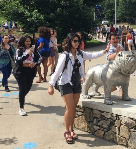 Students pat the Rocky bulldog statue as the walk in to Convocation
