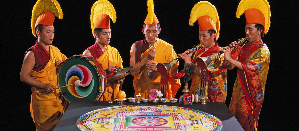 monks with traditional instruments around sand mandala