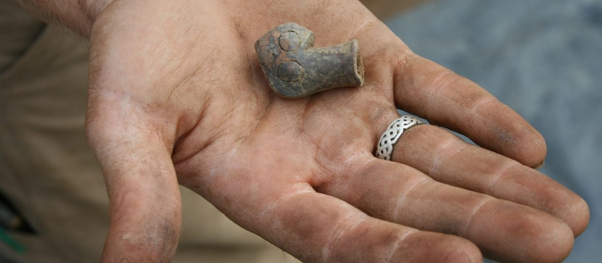 hand holds small piece of clay pipe artifact