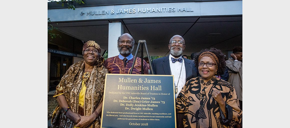 the four professors stand with the building plaque