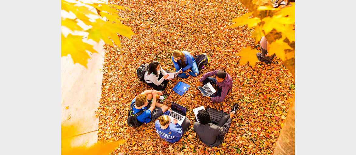 Students among fall leaves