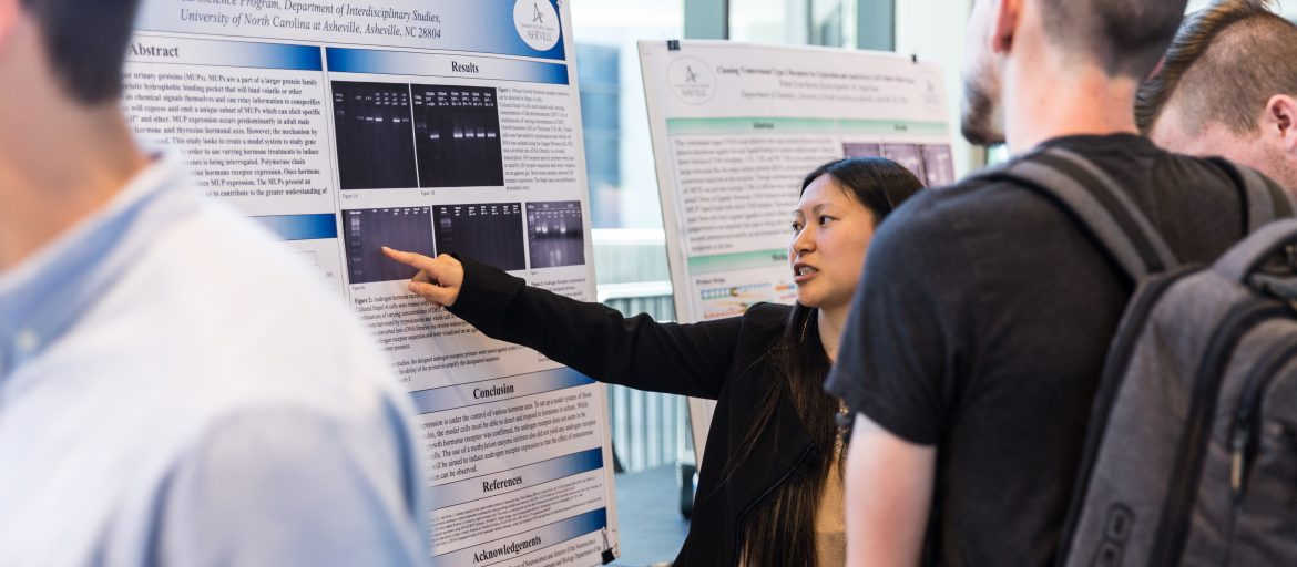 Student at Undergraduate Research Symposium with her poster presentation
