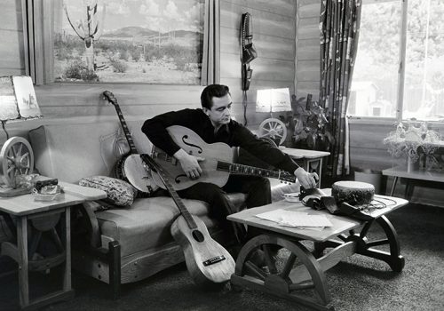 Johnny Cash with guitars at his home in 1960