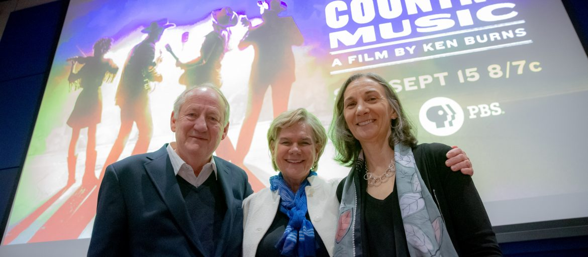 Three people smiling in front of the Country Music documentary image.