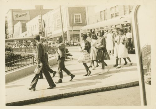 Photo shows well-dressed African Americans crossing a downtown Asheville street; part of the Isaiah Rice Collection