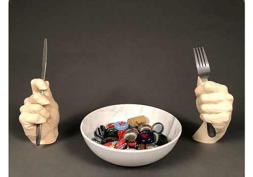 two scuplted hands hold fork and knife, with a bowl of bottle caps between them