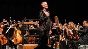 Composer John Luther Adams stands before an orchestra facing the audience with hand on heart