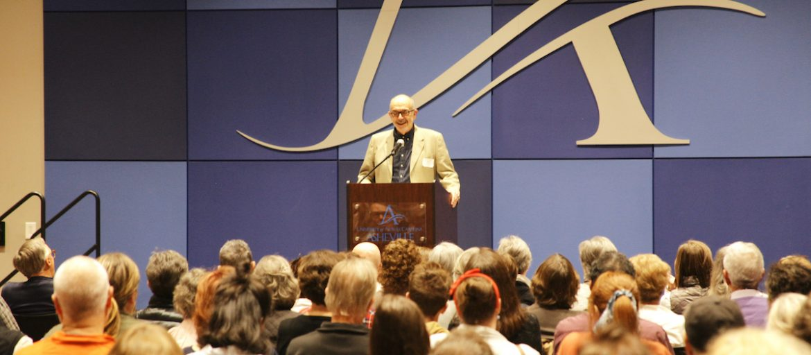 a man at a podium in front of a crowd