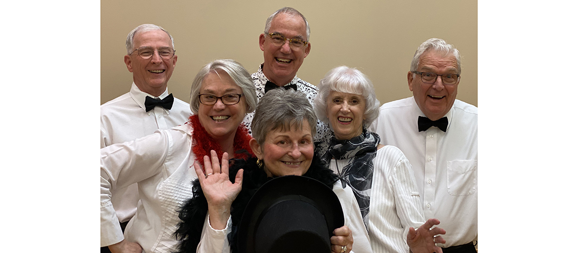 Six members of the Reuter Center Singers pose in formal attire with cheery smiles
