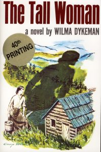 """Book cover of """"The Tall Woman"""" show a woman casting a shadow larger than a house"""