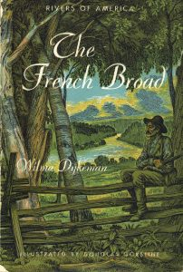 Book cover of The French Broad shows a man sitting on a fence overlooking the river