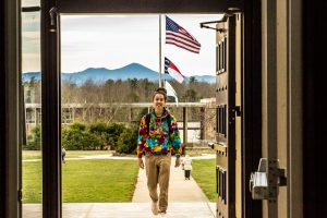 Student walking into Ramsey Library with mountains in the background