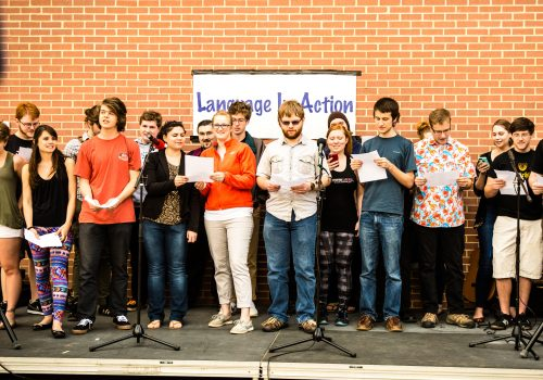 Students on stage reading during language and cultures in action day.