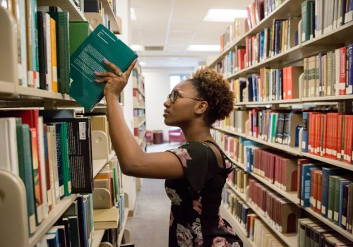 A student taking a book off a shelf at UNC Asheville's Ramsey library.