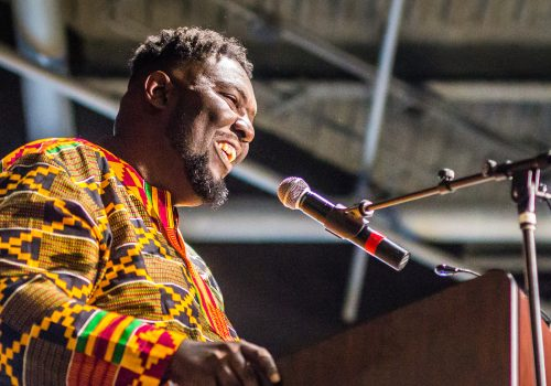 A close-up of a speaker at a podium in traditional African clothing.