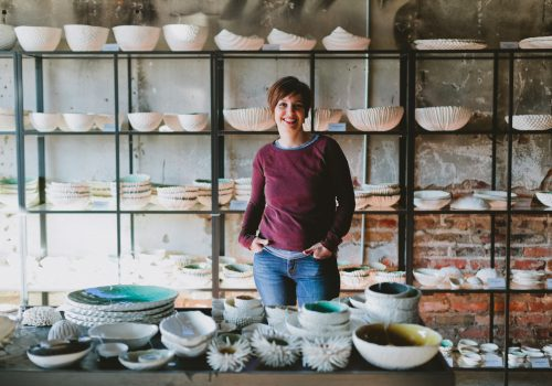 A student standing behind a table with ceramic plates and bowls.