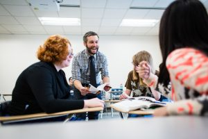 English professor Kirk Boyle works with a small group of students