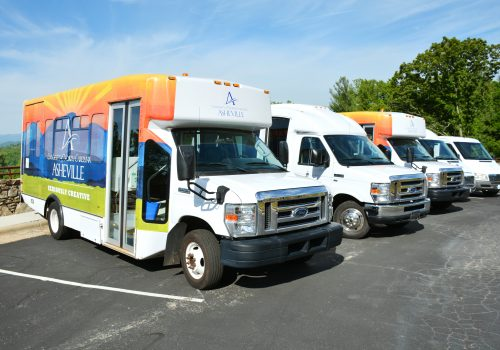 three UNC Asheville shuttles in parking lot