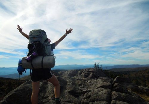 Backpacker standing on an overlook with arms outstretched