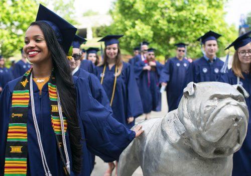 Graduate patting Rocky statue