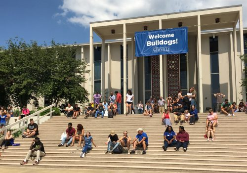 Students at orientation sitting on Ramsey Library steps with Welcome Bulldogs banner in background
