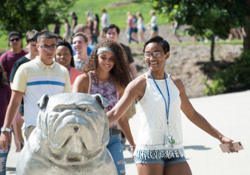 Student patting Rocky the Bulldog statue