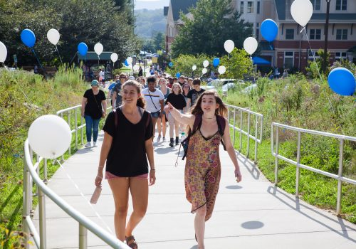 Students walking up towards the Quad with balloons on Move-In Day