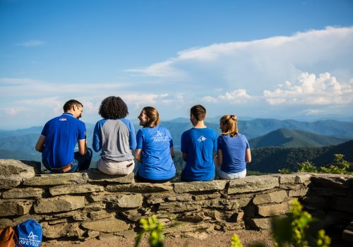 Students sitting on a ledge overlooking the mountain