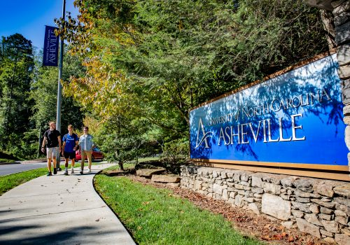 Students walking by the UNC Asheville sign on the greenway