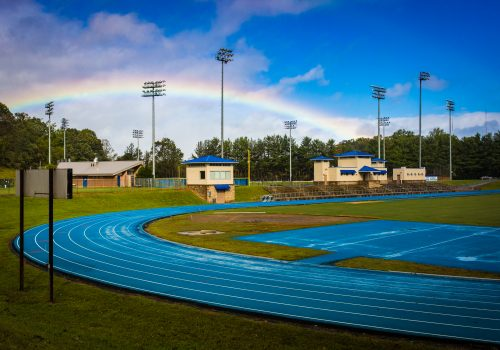 A track with bleachers and a rainbow behind it.
